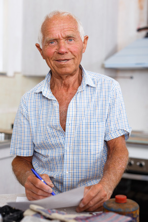 Enthusiastic older man planning upcoming repairs at his home, making list of works Stock Photo