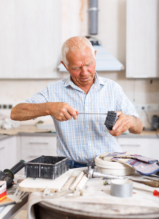Confident senior man working on overhauls of his apartment