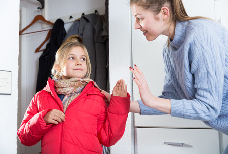 Mother says goodbye to her little daughter in the hallway at home Stock Photo