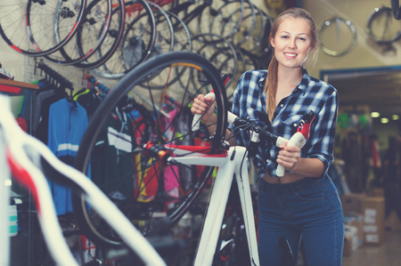 Portrait of happy positive glad girl who is standing with bicycle in store.