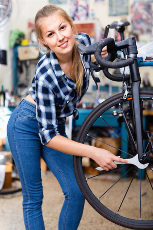 Young smiling female is fixing wheels of bicycle in workshop.
