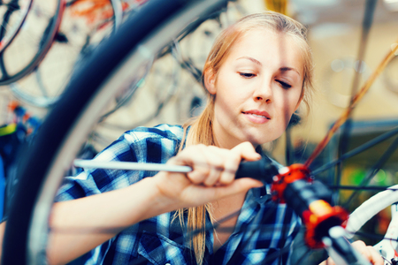 Young happy   woman master is repairing bicycle in workshop. 免版税图像