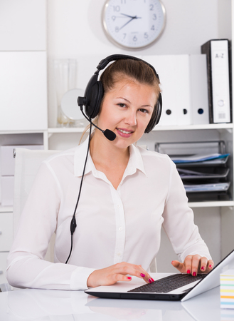 Young woman is working at a computer and talking by headset with client in the office. Foto de archivo