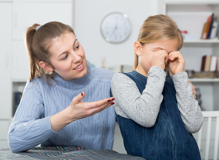 Mother soothes little daughter after an quarrel