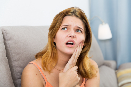 Sad young female on sofa holding hand on the illness tooth