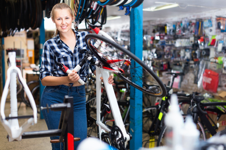Portrait of  positive smiling woman who is standing with new bicycle indoors.