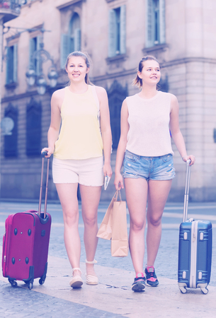 cheerful italian female tourists  exploring old european city with baggage Stockfoto