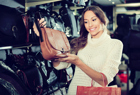 glad woman buying leather purse in haberdashery shop