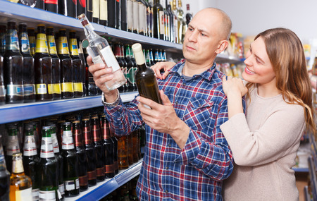 Portrait of family couple choosing alcohol products in a hypermarket Фото со стока - 119206985