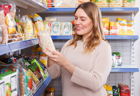 Adult woman customer selecting groats in  grocery food store Stock Photo