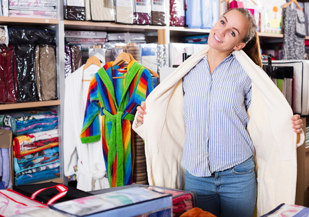 Young woman trying on new bathrobe in textile shop