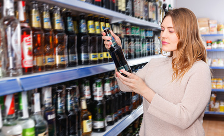 Portrait of smiling cheerful positive woman customer buying bottle of beer in the supermarket