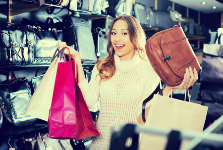 Positive female choosing bag among assortment in store Фото со стока - 119196735