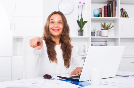 Positive brunette woman in formalwear working on laptop and pointing with finger in company office