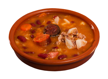 Delicious Fabada asturiana with stewed beans, pork, morcilla and chorizo served in traditional clay cazuela. Isolated over white background