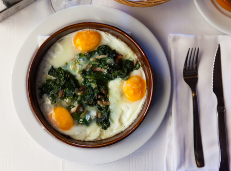 Top view of traditional Catalan fried eggs with spinach, raisins and ham served in clay cazuela Stock Photo