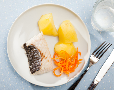 Top view of healthy dietary steamed hake fillet served with potatoes and grated carrot on white plate Stock Photo