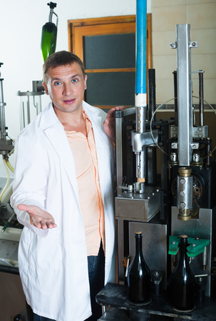 Male assembly line operator in white robe working in modern wine factory