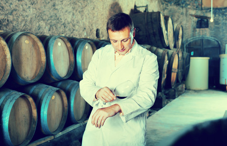 Glad positive  professional taster posing with glass of wine in winery cellar Reklamní fotografie