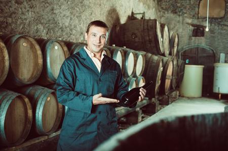 Male winery technician posing with bottle of wine in cellar