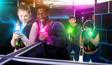 Fine laser tag players of different nationalities aiming laser guns at other players during lasertag game in dark room