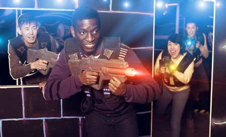 Portrait of happy  smiling African-American with laser gun having fun on dark laser tag arena Stock Photo