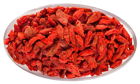 Top view of red dried goji berries in oval glass bowl. Isolated over white background