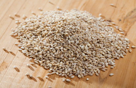 Natural background - organic pearl barley on wooden surface