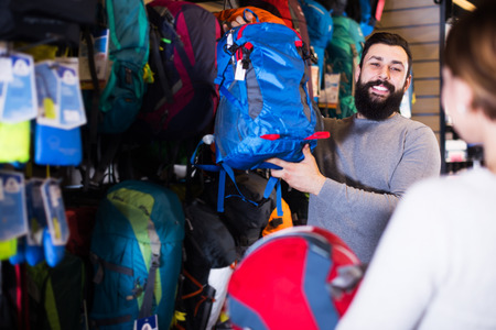 Young couple selecting new rucksack in sports equipment store Stock Photo