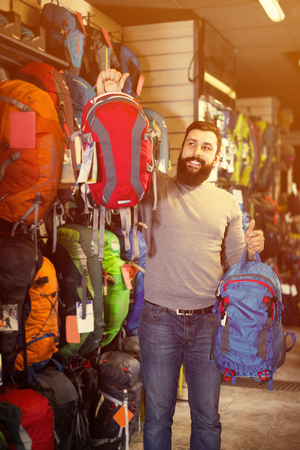 Smiling man customer examining backpacks in sports equipment store