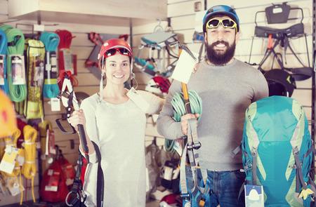 Young couple choosing climbing equipment in sports equipment shop