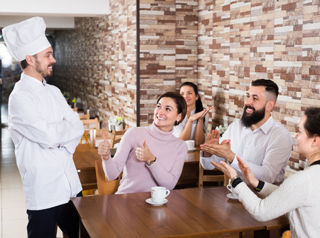Emotional chef listens to praise of the food in café