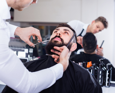 Young  pleasant  male hairdresser accurately cutting beard of client at hair salon