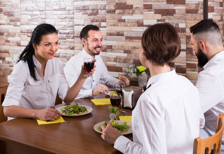group of joyous friends eating at restaurant table and chatting