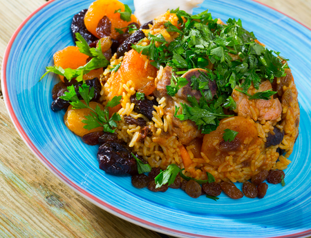 Flavored pilaf from mutton meat with dried apricots, prunes, saffron and sweet garlic Stock Photo