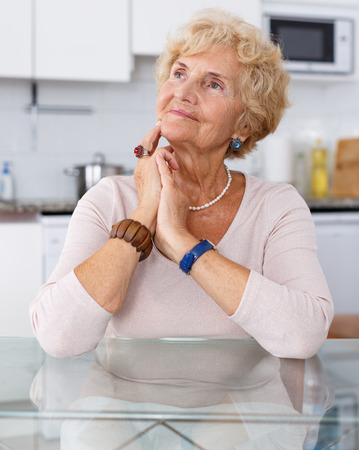 Positive mature woman sitting at kitchen table Imagens