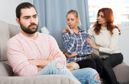 Sad man sitting  after quarrel and girl with mother on background at home
