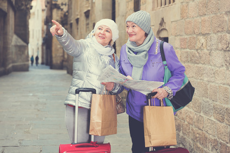 Happy mature ladies travellers with suitcases visiting sights of European city with map
