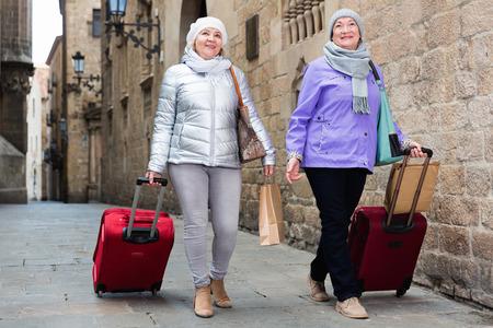 Happy traveling elderly women strolling with luggage along city street