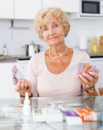 Positive senior woman sitting at kitchen table among a lot of medicines Imagens