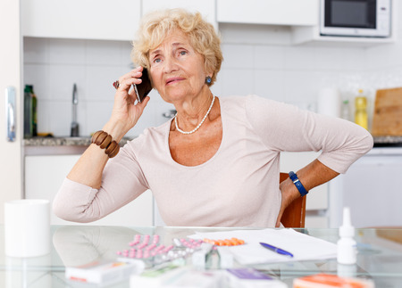 Confused senior woman sitting at kitchen table among a lot of medicines and talking on phone
