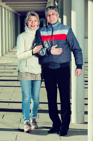 Cheerful husband and wife are walking together clear sunny day between columns