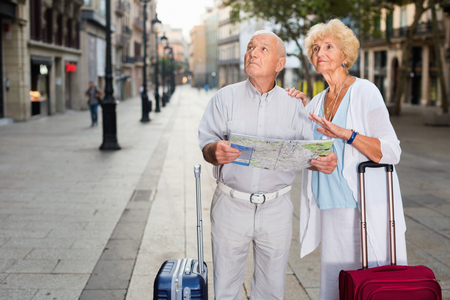 Cheerful smiling senior couple of tourists with map and city guide walking on street