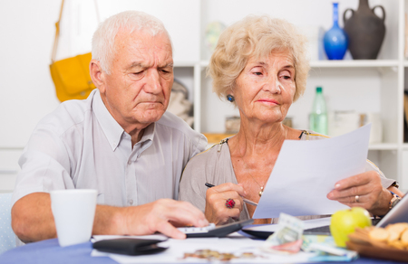 Serious retired couple calculating bills with laptop and calculator at home Фото со стока