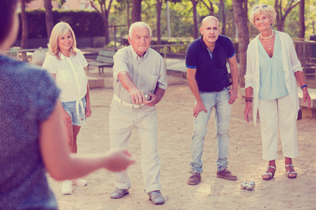 Cheerful positive  family playing petanque in outdoor