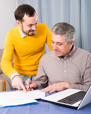 Mature man and young sales manager discuss conditions of contract at home