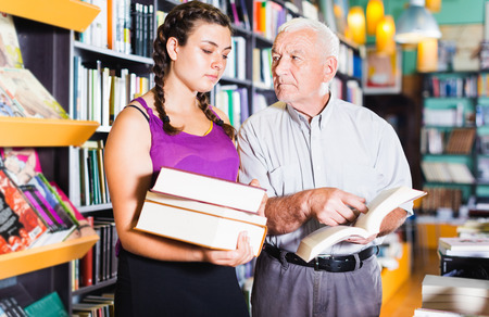 Senior man with young granddaughter are reading books together in bookstore.