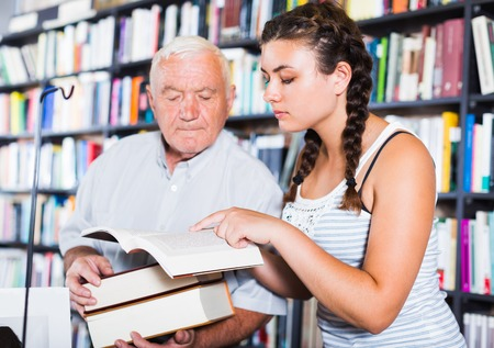 Old man with young granddaughter are reading books in bookstore. 写真素材