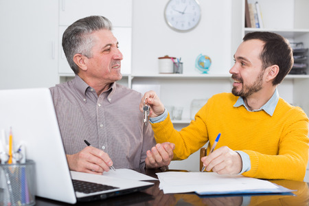 Mature man and young agent sign rental agreement in agency and hand over keys 版權商用圖片