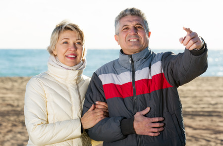 Cheerful mature couple walks outdoors and point by hand to interesting objects